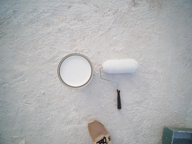 새로운 페인트 롤러와 시멘트 지붕에 페인트 통을 방수 처리합니다.