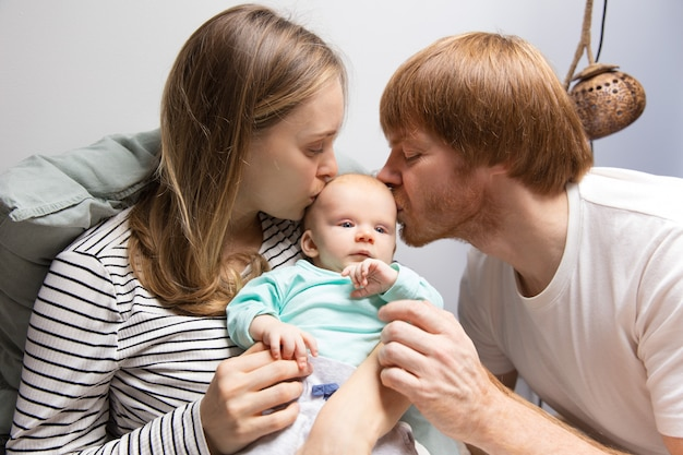 New parents kissing red haired baby head