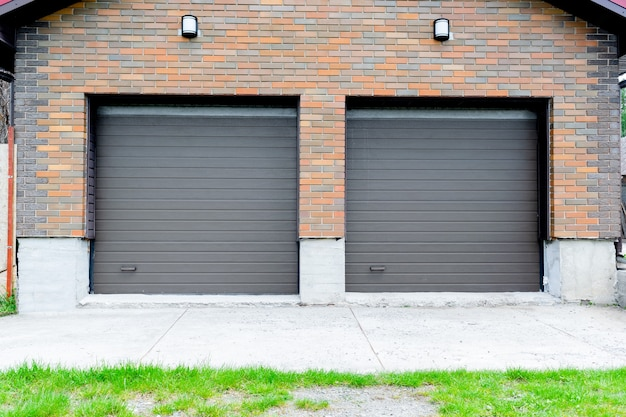 New parking garage in luxury brick house for two cars construction with roller shutters on gates