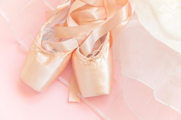 新しいパステルベージュのバレエシューズ、サテンのリボンとピンクの背景に分離されたtututスカート