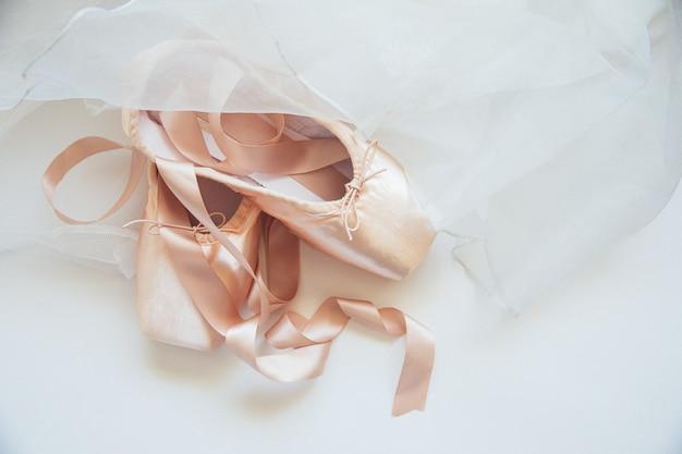 新しいパステルベージュのバレエシューズ、白いテーブルに分離されたサテンリボンとツツルのスカート
