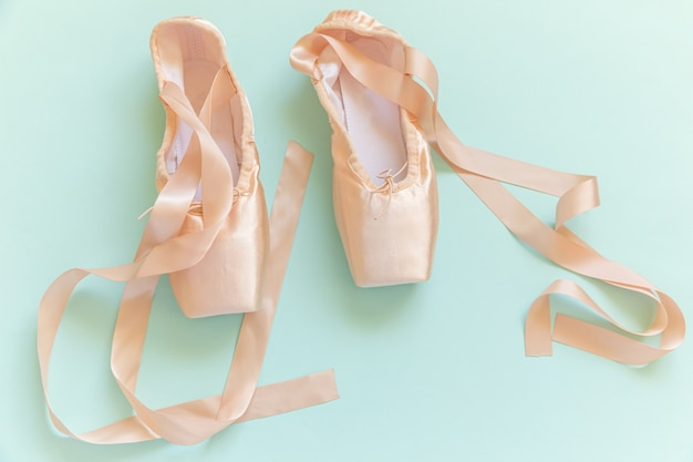 New pastel beige ballet shoes with satin ribbon isolated on blue table