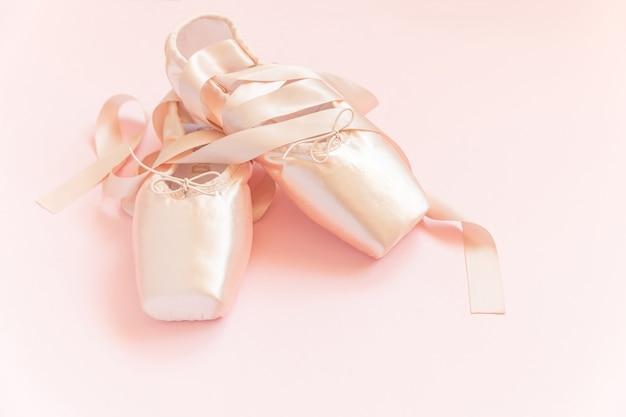 ピンクの背景に分離されたサテンリボンと新しいパステルベージュのバレエシューズ Premium写真