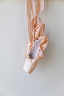 白い背景で隔離のサテンリボンと新しいパステルベージュのバレエシューズ。ダンストレーニング用のバレリーナクラシックトウシューズ。バレエスクールのコンセプト、コピースペース
