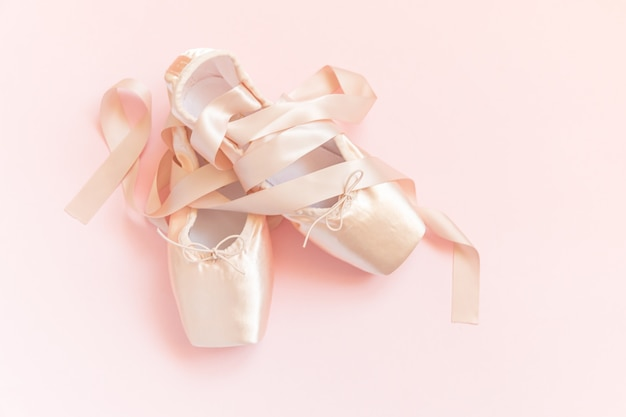 New pastel beige ballet shoes with satin ribbon isolated on pink table