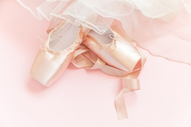 New pastel beige ballet shoes with satin ribbon and tutut skirt isolated on pink table