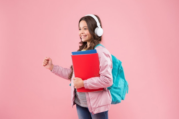Новый взгляд на обучение. счастливый ребенок обратно в школу розовый backgroud. маленький ребенок притворяется, что держит что-то в руке. 1 сентября. день знаний. образование и учеба. начало учебного года, копия места.