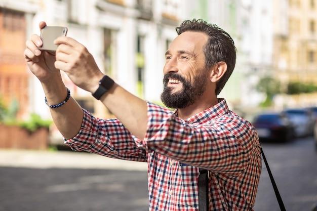 新しい写真。仕事に行きながらストリートビューの写真を作るうれしそうなハンサムな男
