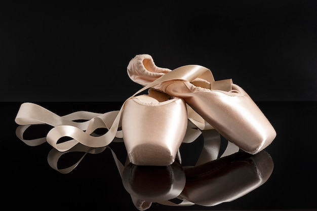 New pink ballet pointe shoes on black background