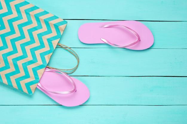 青い木製の背景に新しいピンクのビーチサンダルと紙袋。ショッピングのコンセプト。上面図