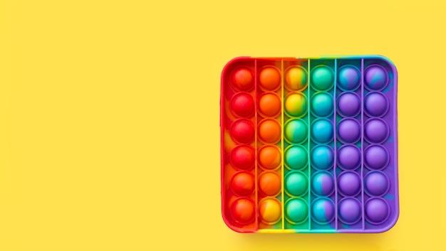 新しい人気のシリコンカラフルなアンチストレスは、黄色の背景に子供のためのおもちゃをポップします。上からの眺め。スペースをコピーします。シンプルなディンプル。