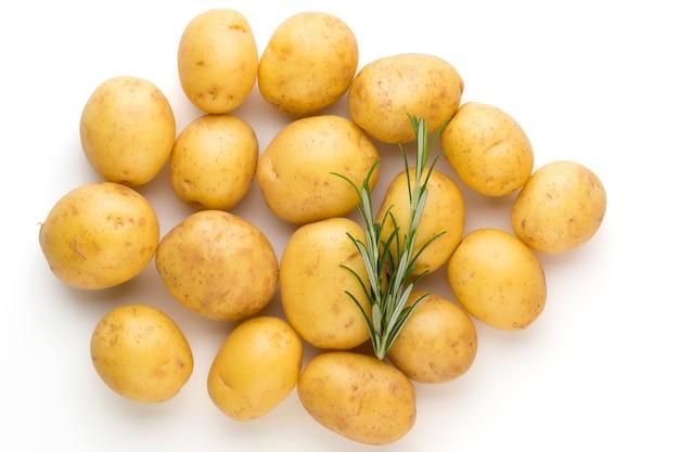 Новый картофель и розмарин, изолированные на белом столе