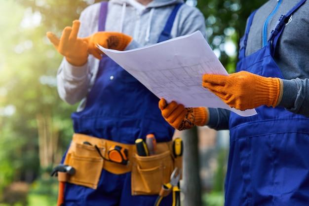 새로운 과제. 코티지 건설에 대해 논의하는 열린 청사진을 들고 야외에 서 있는 두 건축업자의 클로즈업 샷