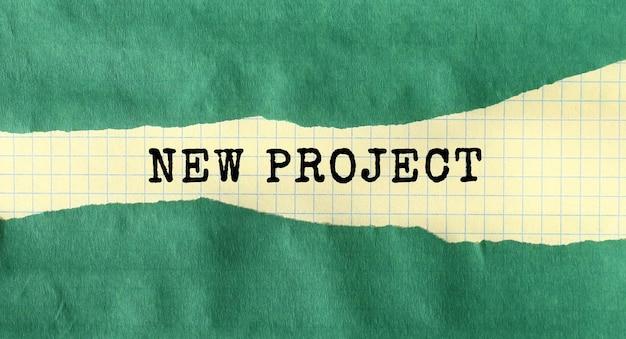 緑の破れた紙の下に書かれた新しいプロジェクトメッセージ