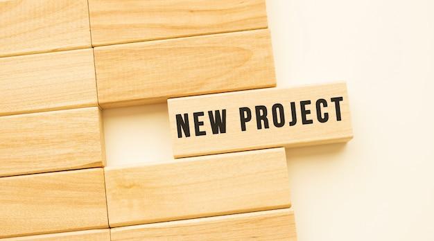 白いテーブルの上に横たわっている木のストリップ上の新しいプロジェクトのテキスト。概念。