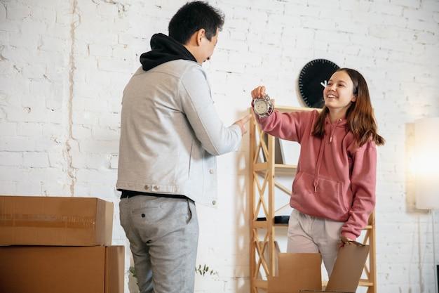 Молодая пара владельцев новой недвижимости, переезжающая в новую домашнюю квартиру, выглядит счастливой
