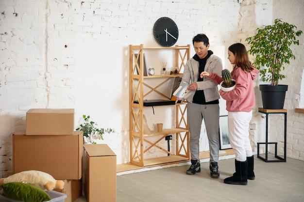 新しい家のアパートに移動する新しい不動産所有者の若いカップルは幸せそうに見えます