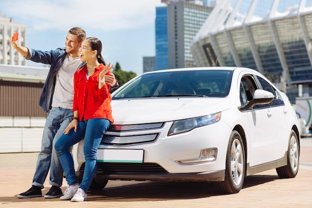 新規購入。自分撮りをしながら車の近くに立っているうれしそうな幸せなカップル