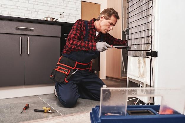 Установка нового холодильника старший техник-мужчина, проверяющий холодильник
