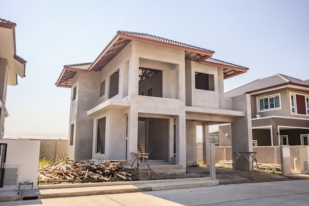 New residential house contemporary style building in progress at construction site with blue sky