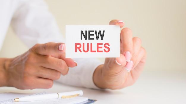 女性の手に白いカードの紙のシートに新しいルールの碑文。白い紙に黒と赤の文字。ビジネスコンセプト、灰色の背景