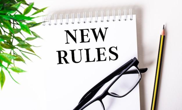 Новые правила написано в белом блокноте рядом с карандашом, очками в черной оправе и зеленым растением.