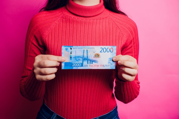 New russian bank notes with vladivostok images on it. 2000 rubles in woman's hand. colored sweater