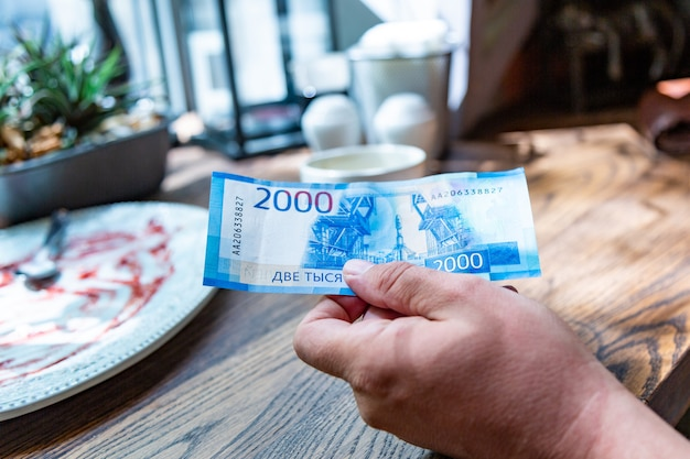 男性の手で2000ルーブル建ての新しいロシアの紙幣、彼はレストランで請求書を支払う予定です