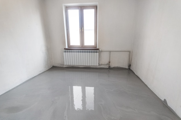 새로운 셀프 레벨링 바닥이 엠티 룸에 부어집니다.
