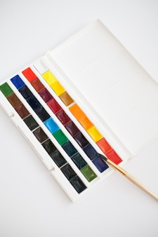 New set of watercolor paints in cuvettes of different colors with a brush on a white table. hobby idea, art school.