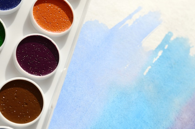 A new set of watercolors lies on a sheet of paper