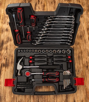 New set of wrenches and bits in tool box on wooden desk. equipment