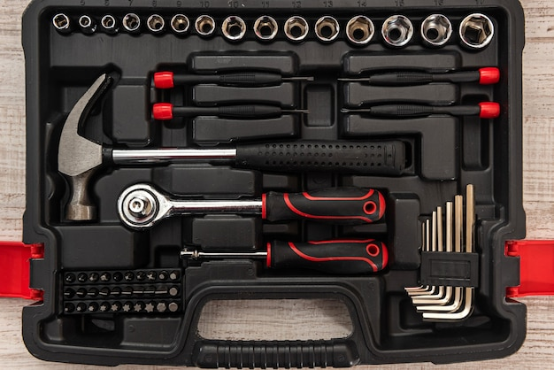 New set of wrenches and bits in tool box on wooden desk