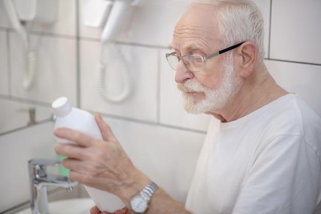 新しいシャンプー。シャンプーのボトルを精査する眼鏡の白髪の男