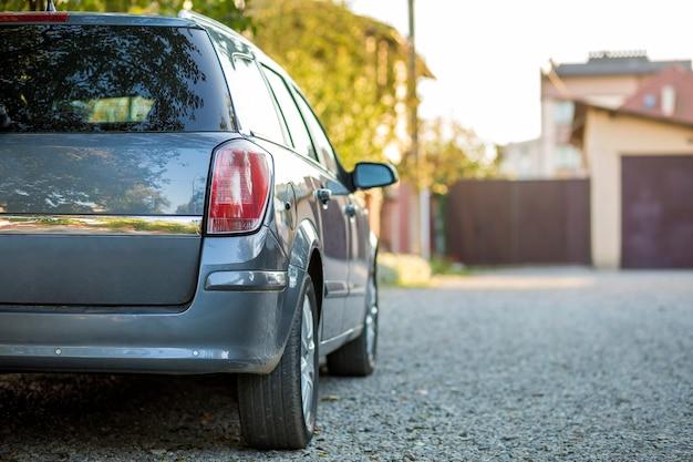 Новый блестящий серый автомобиль припаркован на гравийной дороге в пригороде