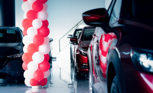 New and shiny luxury suv car parked in modern showroom with sale promotion events. car dealership office. electric car business. automobile leasing. automotive industry. showroom decor with balloons.