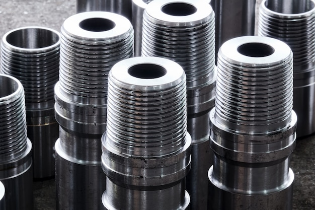 Новые блестящие стальные детали оборудования турбобуров разного диаметра лежат на полу в мастерской