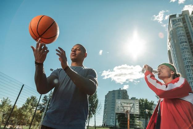 새로운 기술. 그의 친구와 함께 서있는 동안 공을 회전하는 방법을 배우는 즐거운 젊은 남자