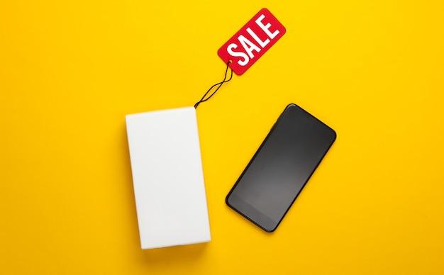 Новый смартфон и коробка с биркой продажи на желтом.
