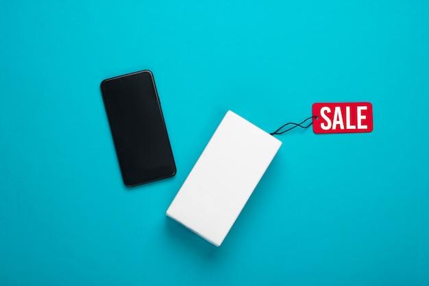 Новый смартфон и коробка с биркой продажи на синем.