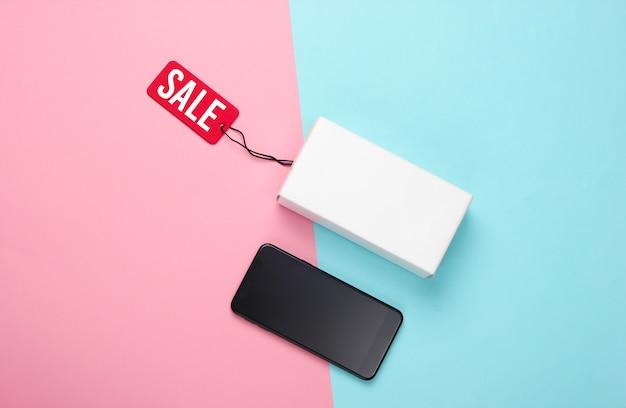 Новый смартфон и коробка с биркой на розово-голубой пастели.