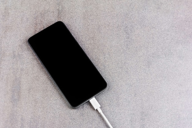 New smartphone with a black screen with a white wire from the charger