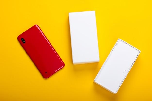 黄色のボックス付きの新しいスマートフォン。新しいガジェットを購入する