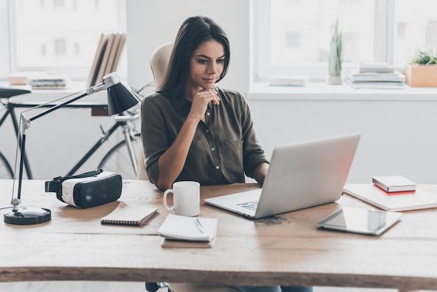매일 새로운 솔루션. 스마트 캐주얼 복장을 한 자신감 있는 젊은 여성이 사무실에서 일하는 동안 노트북 작업을 하고 있습니다.