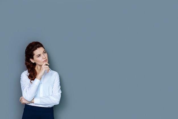 新しいソリューション。あごを持って、新しいアイデアを探しながら自分の仕事について考えている、楽しく陽気な思いやりのある女性