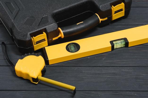 나무 질감 배경에 새로운 사각 검은 도구 상자. 평면도