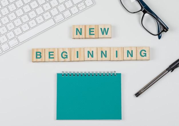 Nuovo inizio e concetto di affari con i blocchi di legno, vetri, tastiera, penna, taccuino sulla disposizione piana del fondo bianco.