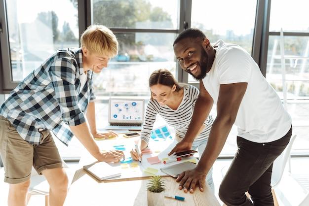 新しいスタートアップ。新しいビジネスのアイデアに取り組んでいて、オフィスに立っている間に彼らのプロジェクトを実行している人々の前向きな若いグループ
