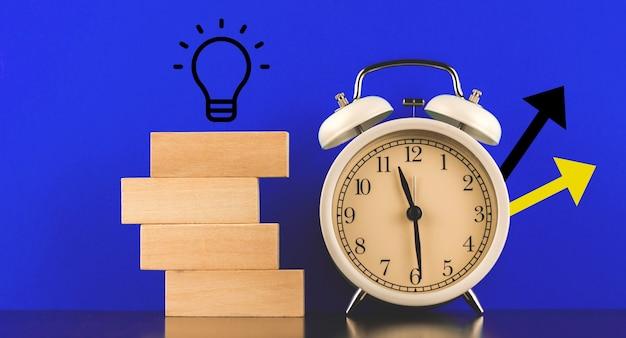 ビジネスマンとフリーランサーのための新しいスタートアップアイデアコンセプトバナー、青い背景とアイコン付き目覚まし時計、テキスト写真の場所