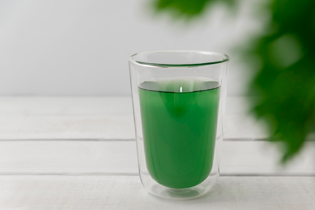 New superfood trend liquid chlorophyll in a cup with water on light background copy space selective ...